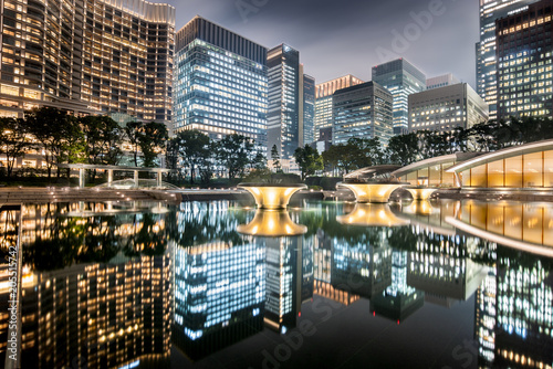 Plexiglas Tokio Cityscape in the Marunouchi business district of Chiyoda with skyscrapers reflected in the fountain taken in a cloudy night, Tokyo, Japan