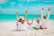 happy family with kids hands up on beach