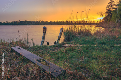 Colorful sunset over the lake in late evening in Spring. Peaceful scenery with clear sky and reflections in water.