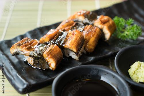 Fotobehang Sushi bar Unagi sushi on black plate along with Japanese sauce and green leaf decoration, Japanese food, close up at sushi..