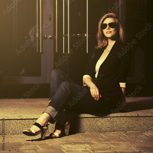 Young fashion woman wearing black blazer and sunglasses sitting at the mall doorway