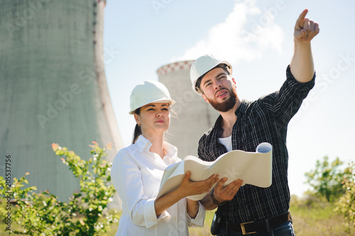 two engineers standing at electricity station, discussing plan