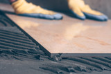 Close-up of a tile stacked on the floor, selective focus, hands of a tiler in the background unfocused - 205543104