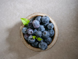 Fresh blueberries, in a ceramic bowl, on a gray background