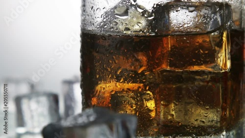 whiskey in a glass with ice on a light background in the contour light. Alcoholic beverages. video rotation