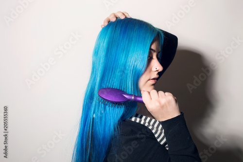 Young woman brushing her long blue hair. Indoors, over a white wall.