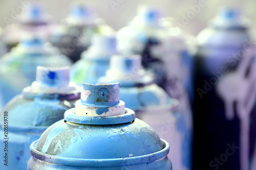 A lot of dirty and used aerosol cans of bright blue paint. Macro photograph with shallow depth of field. Selective focus on the spray nozzle - 205559788