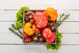Assortment of tomatoes in a wooden box. Fresh vegetables. On a wooden background. Top view. Copy space.