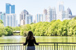 Young woman standing in Piedmont Park in Atlanta, Georgia looking at scenic water, and cityscape skyline of urban city skyscrapers downtown, Lake Clara Meer