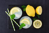 Summer lemonade in two glasses. Top view on a slate server against a dark background.