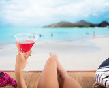 Girl relaxes at the beach with a cold drink