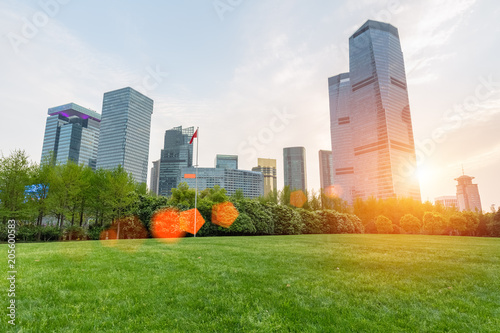 Fototapeta city park lawn with modern building in sunset