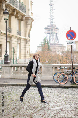 Fotobehang Nice Afro american man running near road sign and bike with Eiffel Tower in background, wearing grey scarf and black sweater. Concept of hurrying and fashionable look.