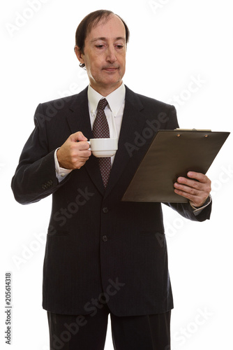 Studio shot of mature businessman holding coffee cup while readi