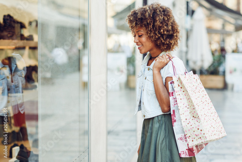 Foto Murales Young black woman, afro hairstyle, looking at a shop window