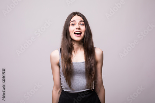 Shocked young woman looking at camera with mouth open isolated on grey