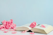 Vintage withered pink pastel rose flowers with open book
