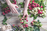 Florist at work. Female hands collect a wedding bouquet of roses. People in the process of work - 205625539
