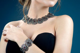 silver jewelry and fashion concept. A model with earrings necklace and ring on dark blue background