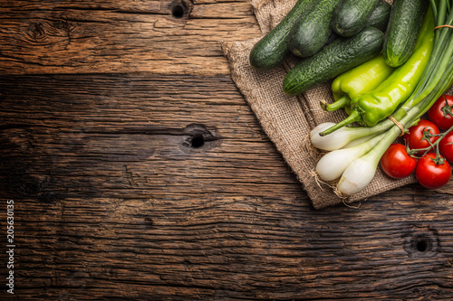 Fresh vegetable onion cucumber pepper and tomatoes on rustic oak table