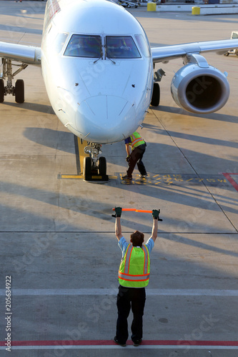 Ground crew signaling to incoming taxing airplane arriving for a spot at the terminal.