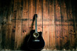 Quadro Acoustic guitar on a wooden texture with copy space for a text. Music and leisure concept. Guitar against wooden wall.