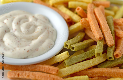 Close view of veggie straws plus a bowl of ranch dressing.