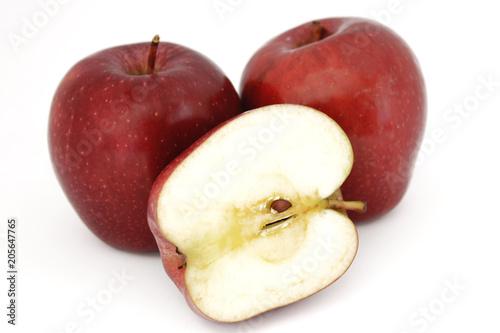 Foto Murales Dos manzanas rojas enteras, sujetan media manzana, partida a la mitad, sobre fondo blanco.