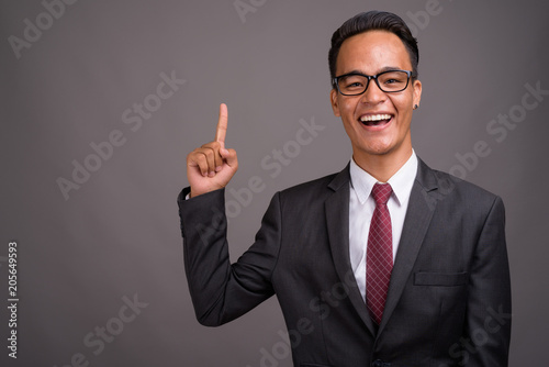 Young handsome Indian businessman against gray background