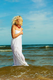 Blonde woman wearing dress walking in water
