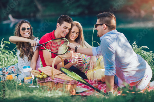 Fototapeta Young people having picnic near the river. Young friends relaxing by the river