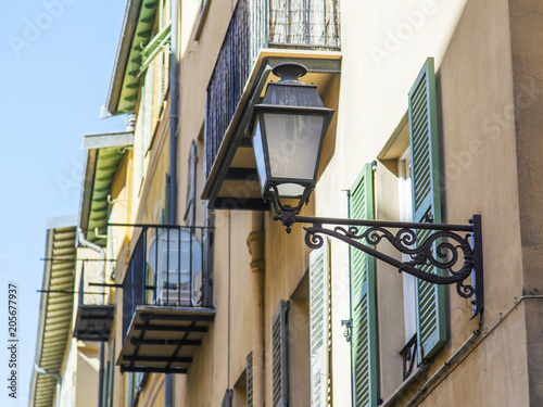 NICE, FRANCE, on March 9, 2018. The sun lights the beautiful ancient lamp decorating a building facade in the old city