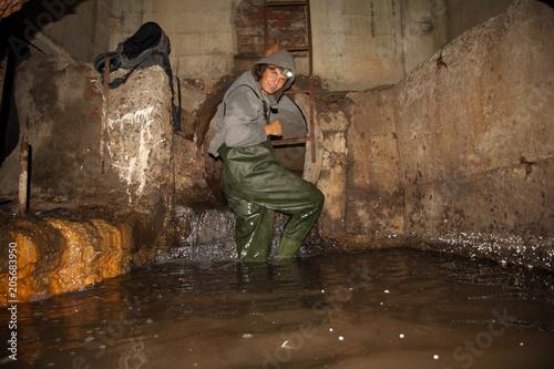 Pracownik kanalizacji w kolektorze podziemnym zalany ścieków