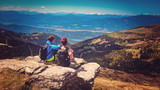 two women sitting on the top of a mountain with wonderful view