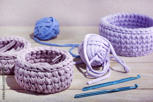 Knitted baskets and skeins of yarn, hook on a wooden table. Handmade crochrting background. - 205704568