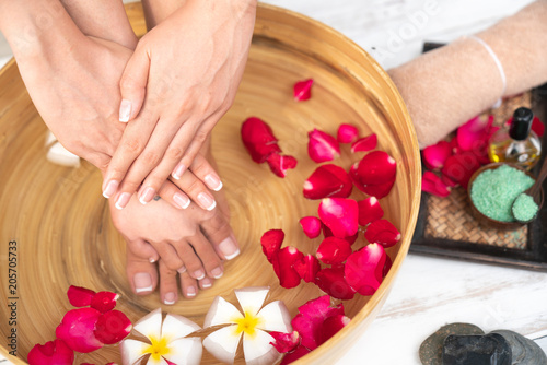 Fotobehang Pedicure Closeup photo of a female feet at spa salon on pedicure procedure. Female legs in water decoration the flowers.