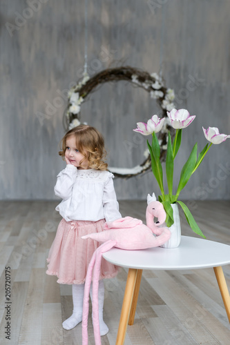 Fashionable little girl posing at a table on which there is a vase with a tulip
