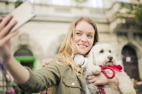 Smiling woman taking a selfie with her dog