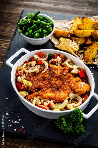 Fotobehang Steakhouse Fried pork chop with vegetables on wooden background