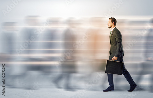 Young businessman with briefcase hurry up on a crowded street with blurred people around  - 205722910
