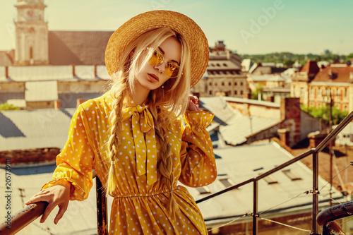 Plenerowy portret młoda piękna dziewczyna jest ubranym modnych żółtych kolorów okulary przeciwsłonecznych, słomianego wioślarza kapelusz, polki kropki smokingowy pozować w ulicie europejski miasto. Koncepcja mody letniej. Kopiuj. Pusta przestrzeń