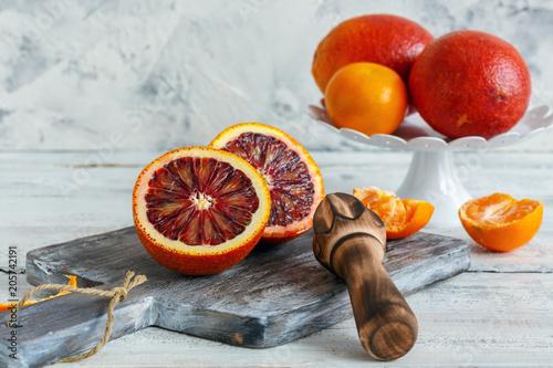 Krwawa pomarańcza przecięta na pół i drewniana prasa cytrusowa.