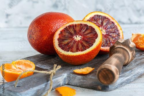Całość i połówki pomarańczy krwi i prasy cytrusowej.