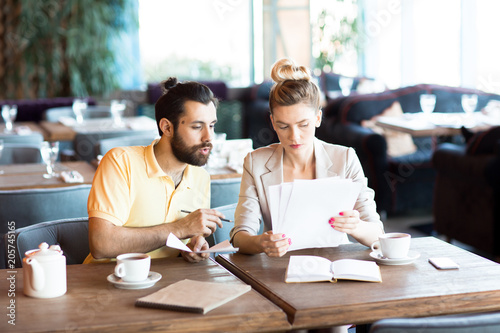 Young serious businesswoman and her co-worker discussing several documents during meeting in cafe