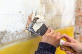 Junge Frau mit Spachtel in der Hand renoviert - 205748340