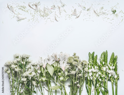 Foto Murales White background with green flowers setting and petals , top view, frame or border