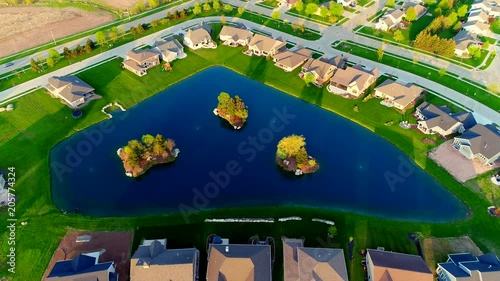 Beautiful homes around stunning pond with islands. Springtime aerial view at sunrise.
