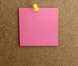 Hoja de papel cuadrada de color rosa, posit, clavado con una chincheta amarilla, en la pared marrón de corcho - 205781355