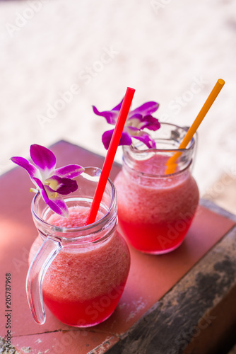 Foto Murales Watermelon Smoothie in glass with watermelon and flower on wooden background