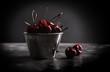 Sweet juicy cherries in metal pail on a table in front of dark background.